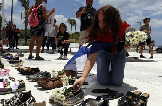 A woman places shoes to represent one of those killed by Hurricane Maria in front of the Capitol in San Juan, Puerto Rico, on June 1, 2018.