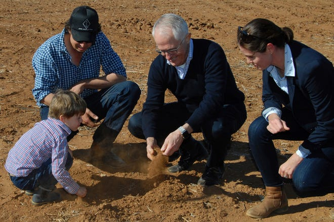 In this June 4, 2018, photo, Australian Prime Minister Malcolm Turnbull, second right, looks at dry soil with farmers during a visit to Strathmore Farm near Trangie, north west of Sydney.