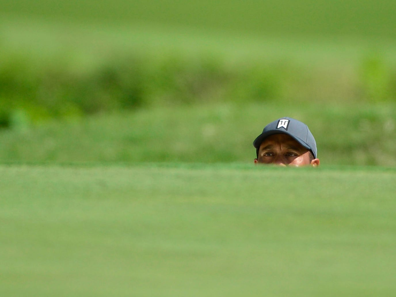 Tiger Woods looks out from a bunker on the 17th hole during the first round of the PGA Championship.
