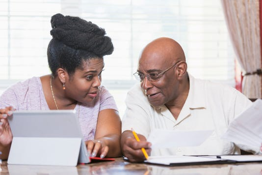 Senior Man And Adult Daughter Working On Home Finances