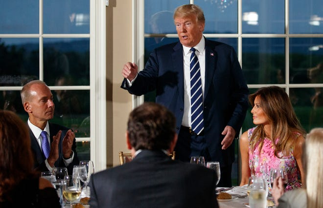 President Donald Trump talks a he walks to his seat between first lady Melania Trump, right, and Boeing Co. Chairman, President and CEO Dennis Muilenburg, left, after speaking at a dinner meeting with business leaders, Tuesday, Aug. 7, 2018, at Trump National Golf Club in Bedminster, N.J. (AP Photo/Carolyn Kaster) ORG XMIT: NJCK112