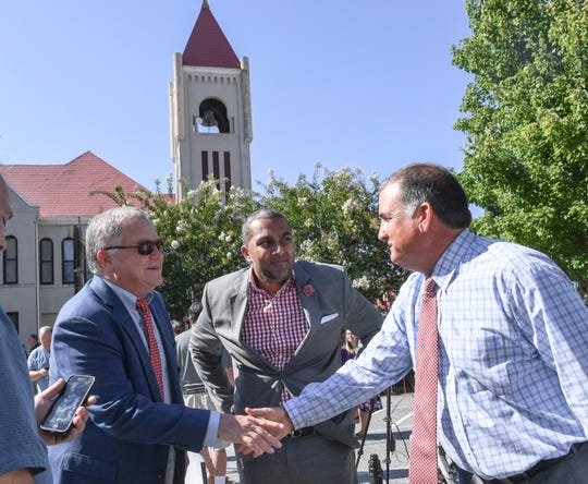 Steve Timmons, left, of Longshot LLC in Greenville, shakes near with Anderson City Councilman Matt Harbin near Mitesh Patel of Paragon Hotel Company in Anderson after the announcement of plans for a $12 million hotel in downtown Anderson on Friday, August 10.