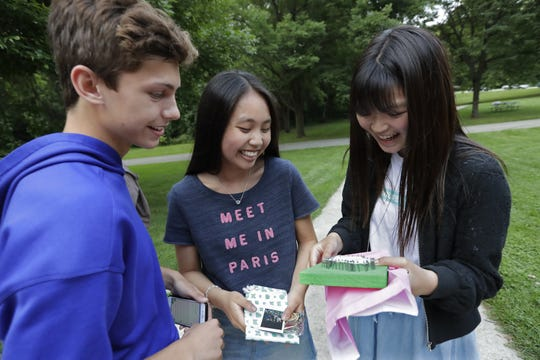 Appleton North High School students Ethan Hughes, 16, left, and Tracy Wang, 16, give gifts to Ramu Yamo, 16, right, of Kanonji, Japan, during a recent farewell picnic at Peabody Park in Appleton. Dan Powers/USA TODAY NETWORK-Wisconsin