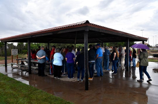 Visitors gather beneath the roof of a pavilion at Kirby Lake to dedicate the new Nature Park Friday. The park features a raised boardwalk through the trees for interacting with the environment and placards highlighting local flora and fauna through pictures.