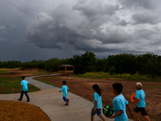 Children from Day Nursery of Abilene walk back to their van as clouds drift south of Kirby Lake Friday. The city's new Nature Park was dedicated as the rain began to abate.