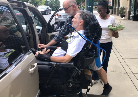 "Charlie Layman helps load his partner, Paul Endry, into a van, while caregiver Daisy Thomas looks on. ""There are times when it's quite difficult and sad, but we've navigated it and we're moving on with our life, and we keep saying, 'The best is yet to come,'"" Layman said."