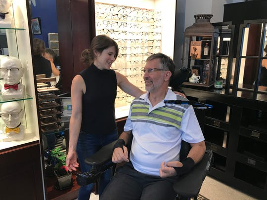 "Optometrist Paul Endry chats with his cousin, Libby Endry, at his office in the Grove Arcade. ""He's a role model for determination,"" she says."