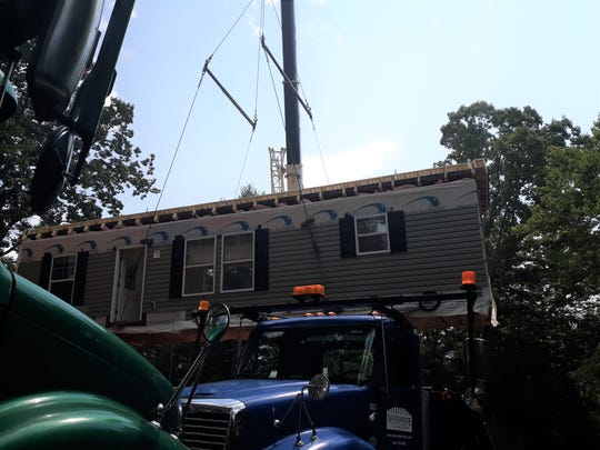 The first half of the Alshaer's modular home being lifted into place.