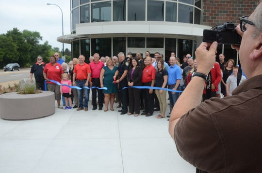 Battle Creek historian Kurt Thornton photographs the ribbon cutting at noon Friday, Aug. 10, 2018 for the new Battle Creek Police Station.