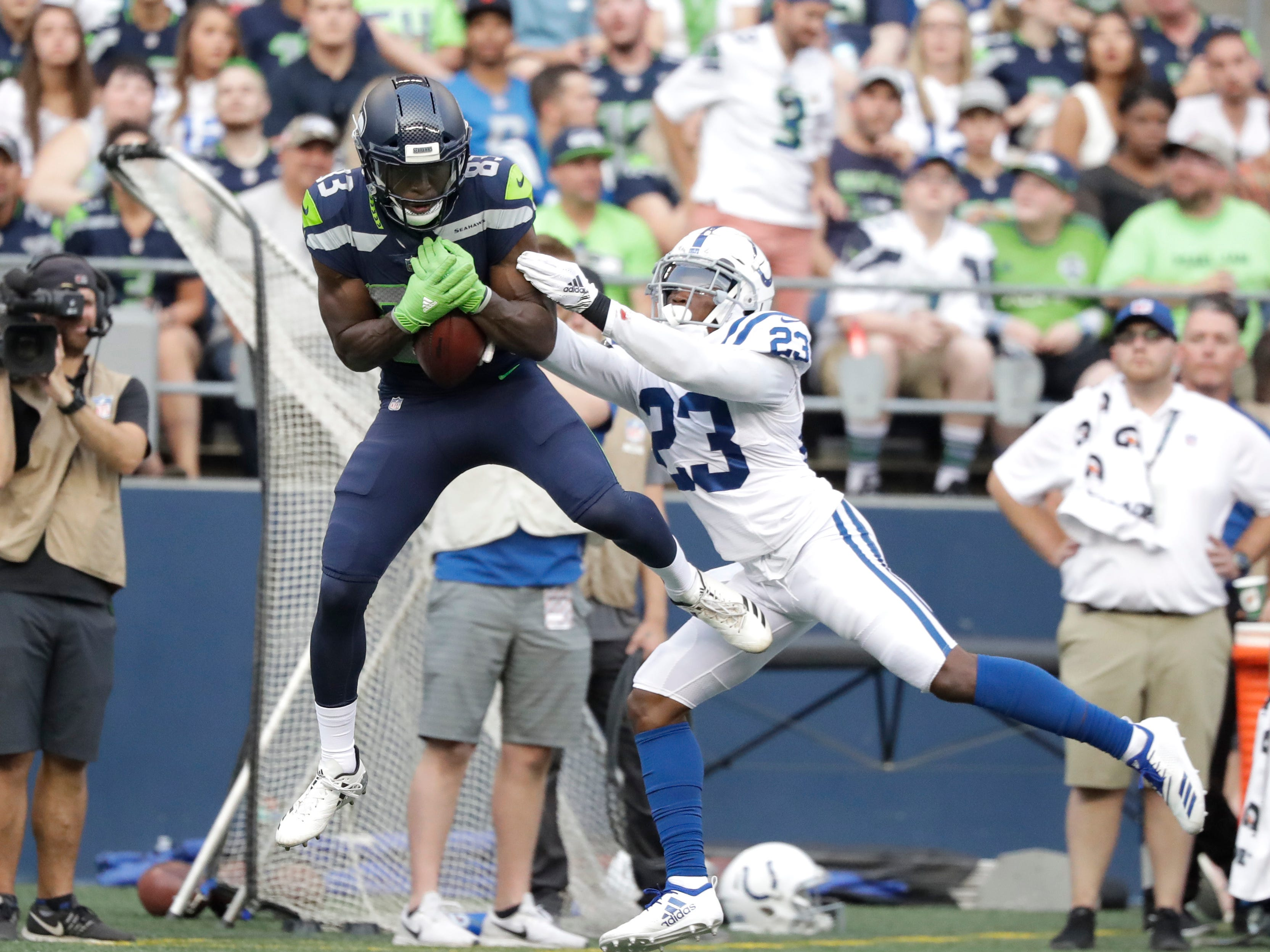 Seattle Seahawks wide receiver David Moore (83) makes a catch above Indianapolis Colts cornerback Kenny Moore (23) during the first half of an NFL football preseason game, Thursday, Aug. 9, 2018, in Seattle. (AP Photo/Elaine Thompson)