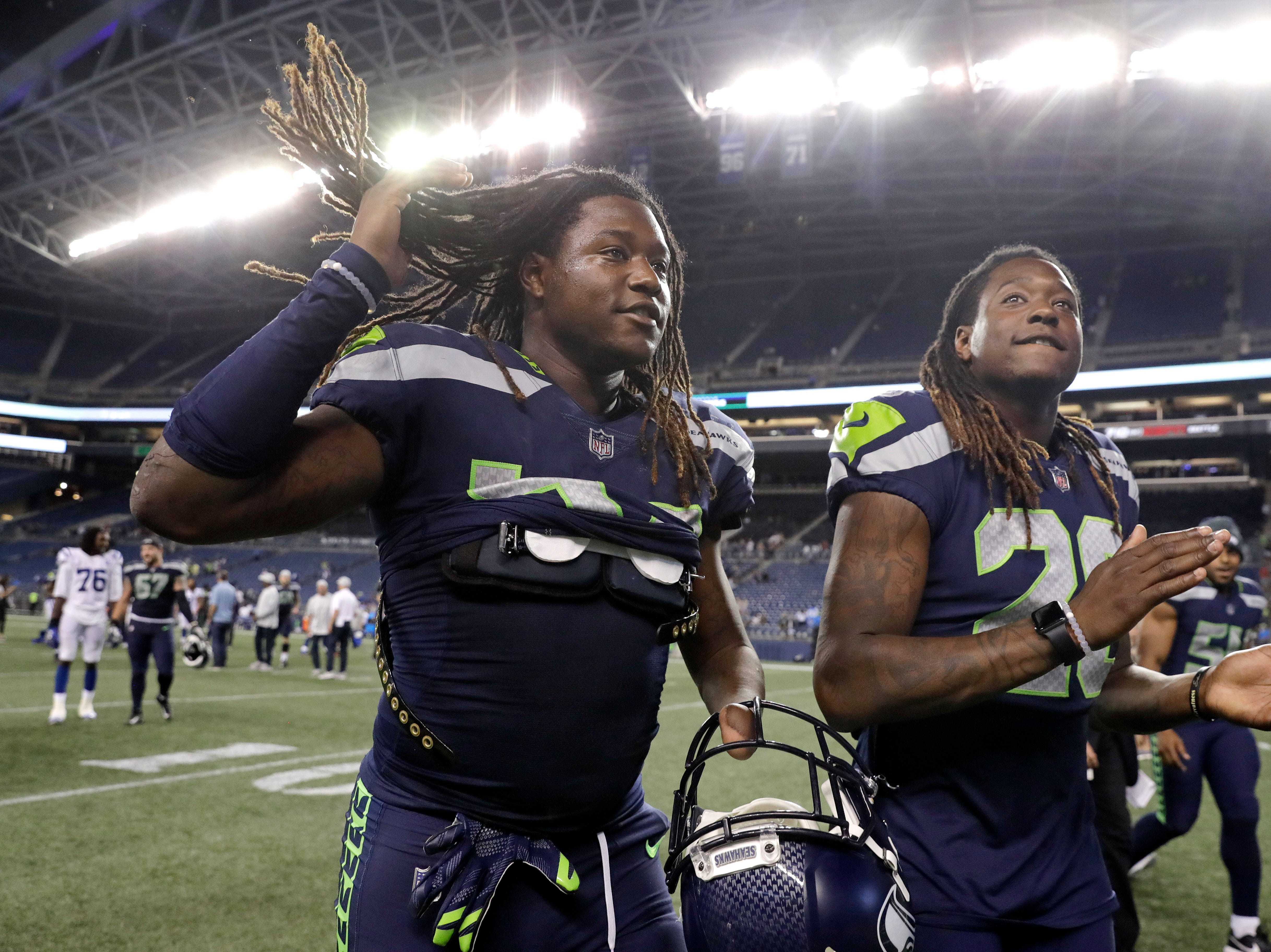 Seattle Seahawks twin brothers linebacker Shaquem Griffin, left, and cornerback Shaquill Griffin leave the field following the team's NFL football preseason game against the Indianapolis Colts, Thursday, Aug. 9, 2018, in Seattle. The Colts won 19-17. (AP Photo/Stephen Brashear)