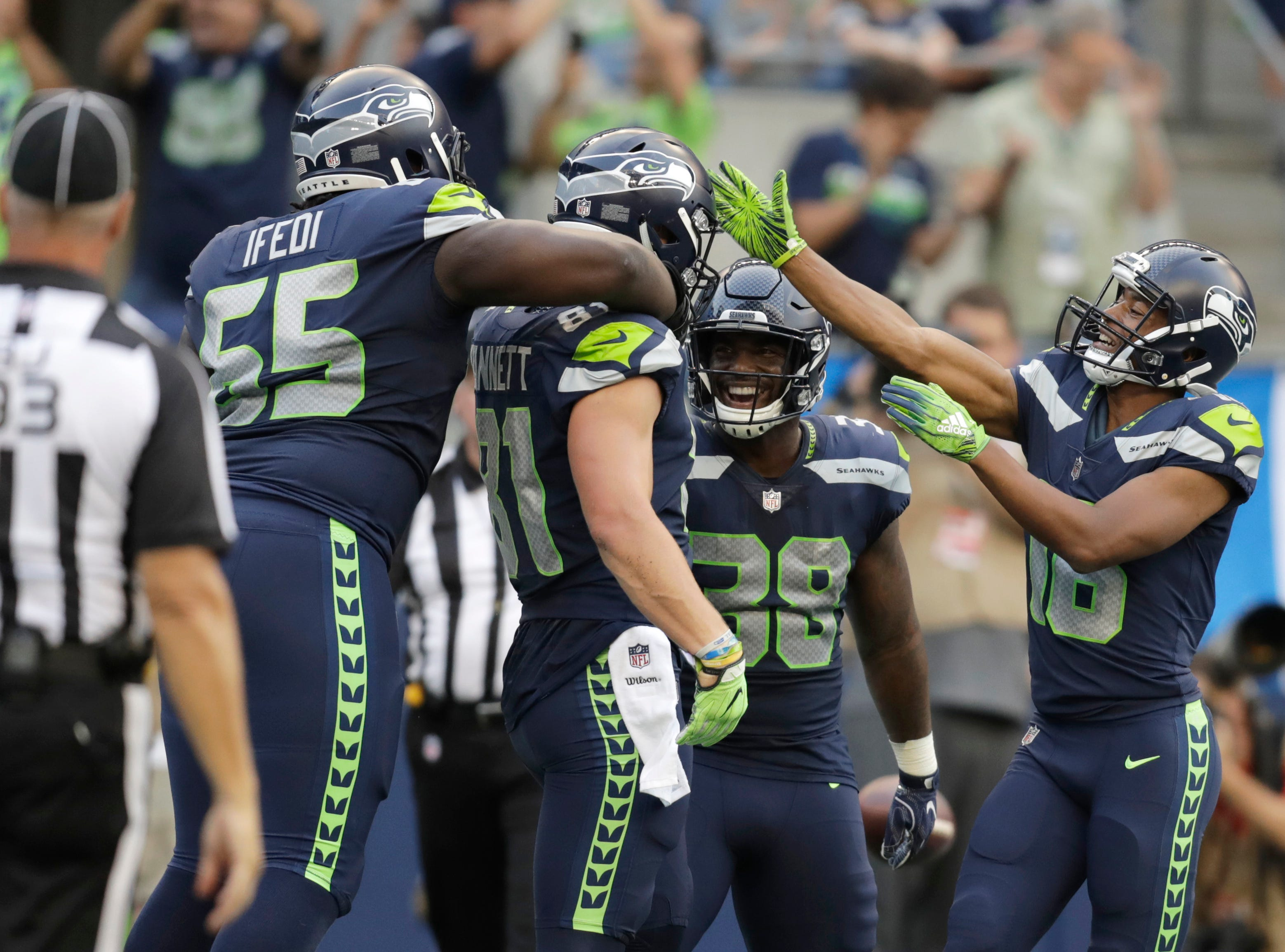 Seattle Seahawks tight end Nick Vannett, second from left, celebrates with teammates Germain Ifedi, left, Tyler Lockett, right, and Tre Madden, second from right, after making a catch for a touchdown against the Indianapolis Colts during the first half of an NFL football preseason game, Thursday, Aug. 9, 2018, in Seattle. (AP Photo/Stephen Brashear)