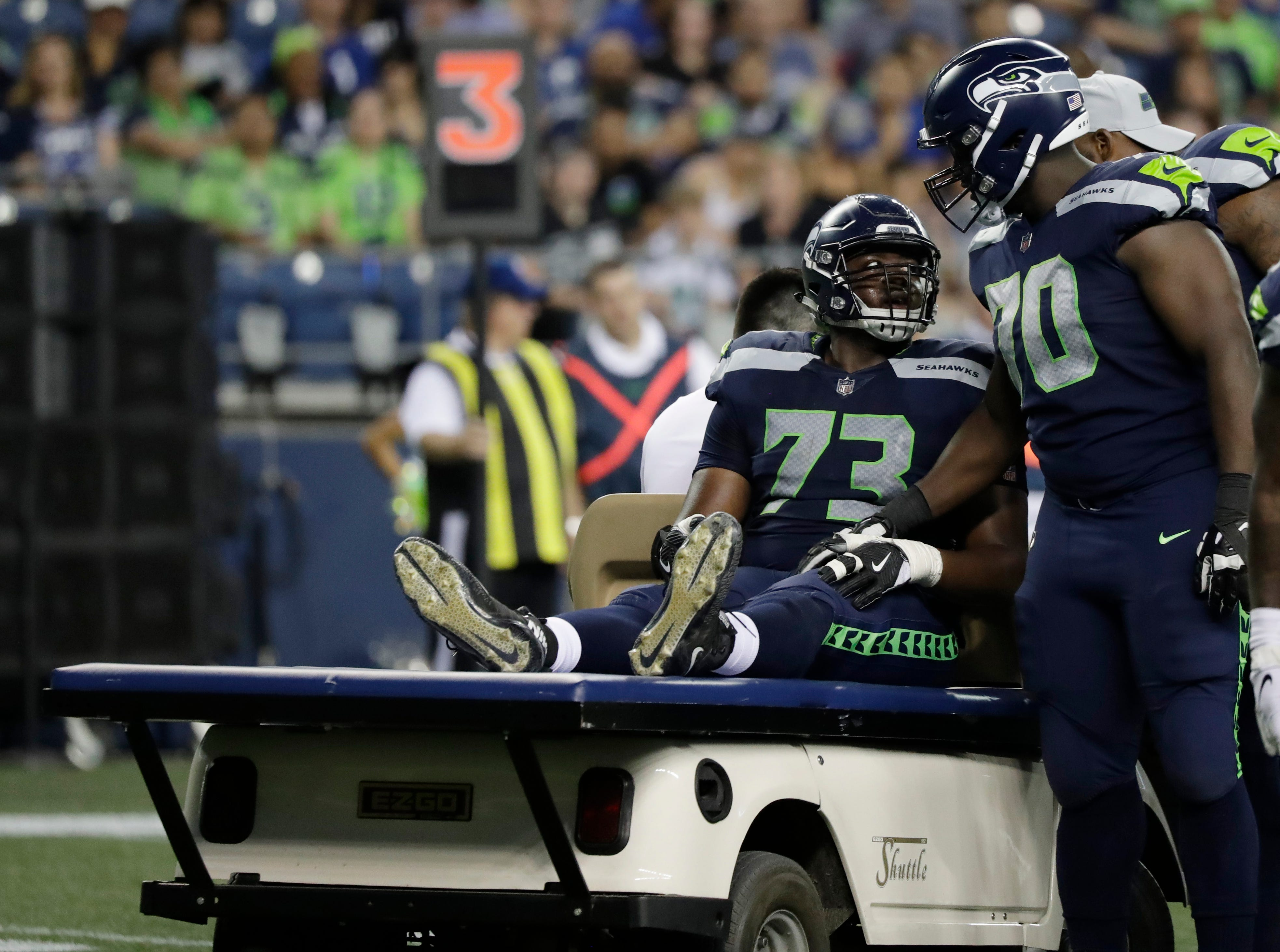 Seattle Seahawks offensive tackle Jamarco Jones (73) is comforted by teammates, including offensive guard Rees Odhiambo, right, as he is taken off the field on a cart during the second half of the team's NFL football preseason game against the Indianapolis Colts, Thursday, Aug. 9, 2018, in Seattle. (AP Photo/Elaine Thompson)
