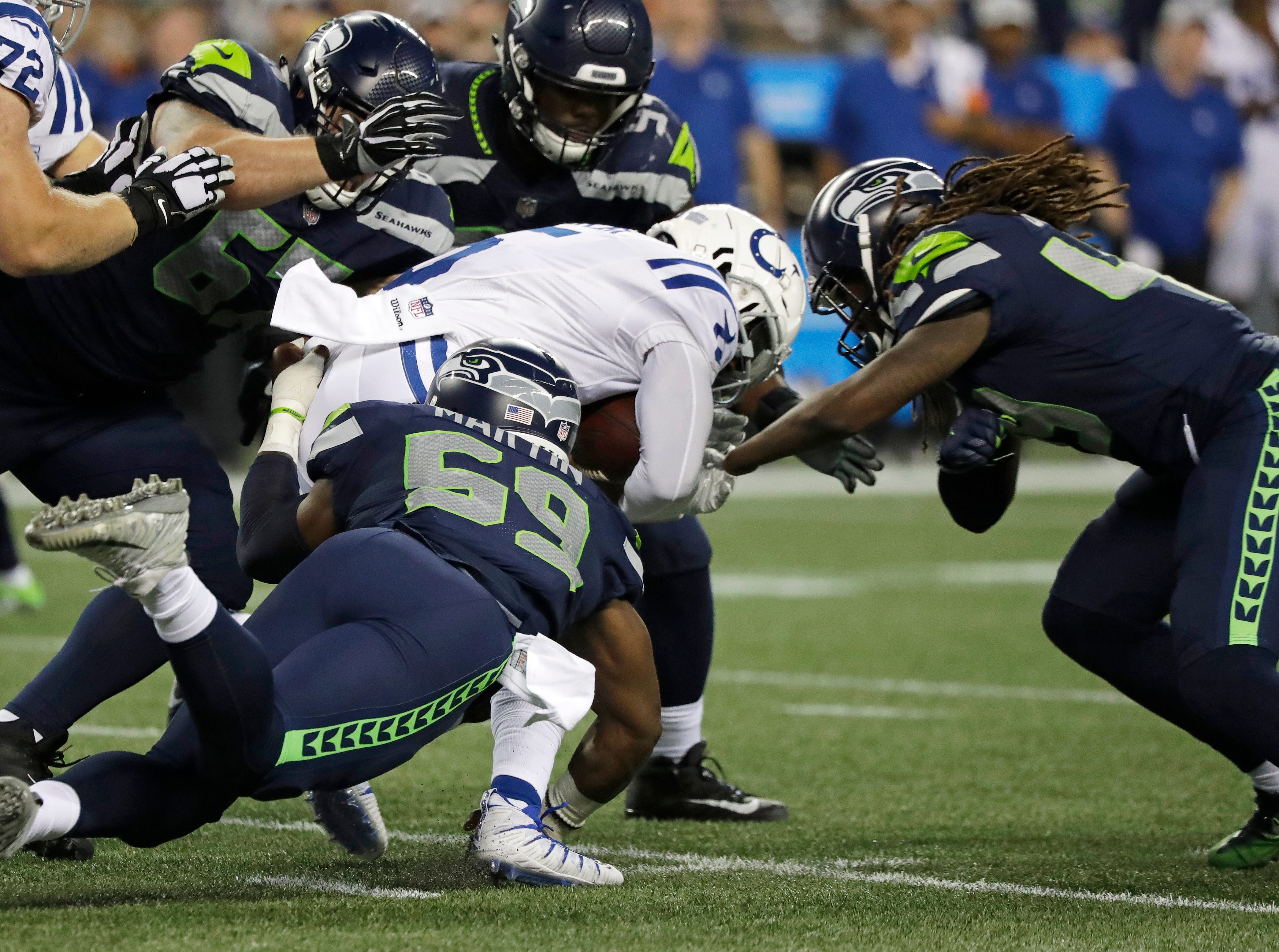 Indianapolis Colts quarterback Phillip Walker, center, is tackled by Seattle Seahawks linebacker Shaquem Griffin, right, and defensive end Jake Martin (59) during the second half of an NFL football preseason game, Thursday, Aug. 9, 2018, in Seattle. (AP Photo/Elaine Thompson)