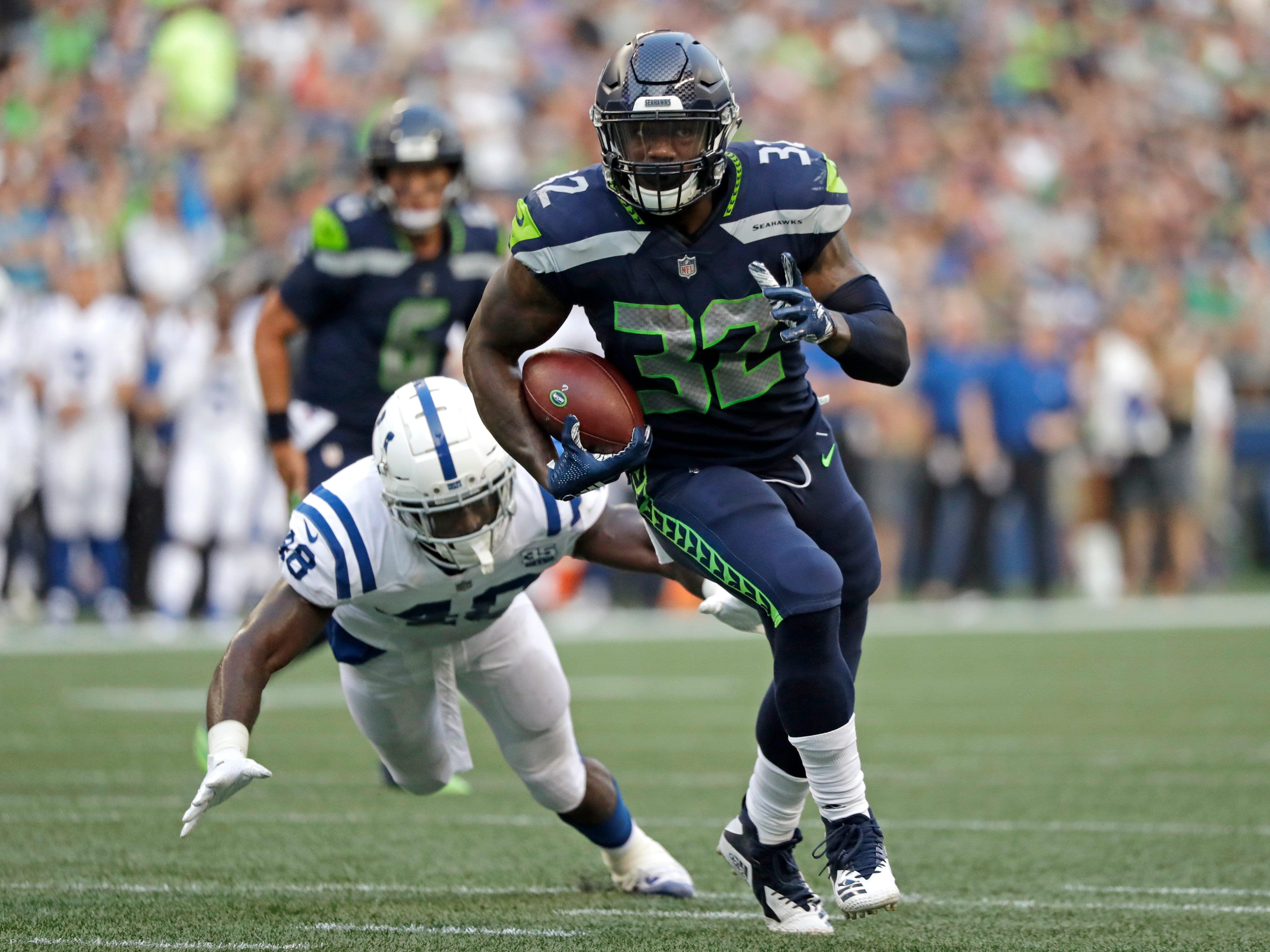 Seattle Seahawks running back Chris Carson (32) outruns a tackle-attempt by Indianapolis Colts linebacker Skai Moore during the first half of an NFL football preseason game, Thursday, Aug. 9, 2018, in Seattle. (AP Photo/Elaine Thompson)