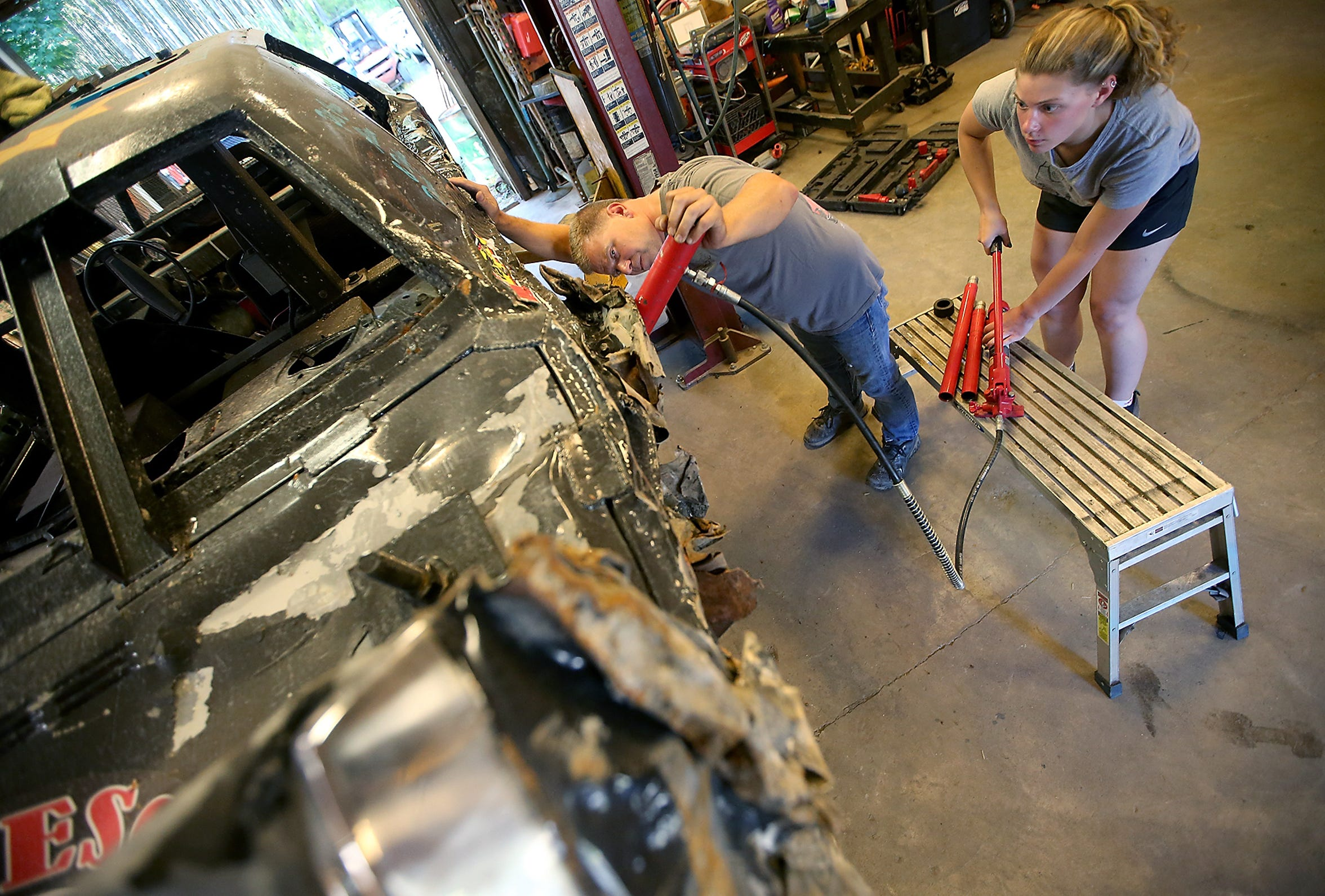 KDDA President Dan Pieze and his daughter, Alison, work on Pieze's car at their Port Orchard home on July 25. Acquiring, fortifying and repairing derby cars can become an obsession for derby drivers.
