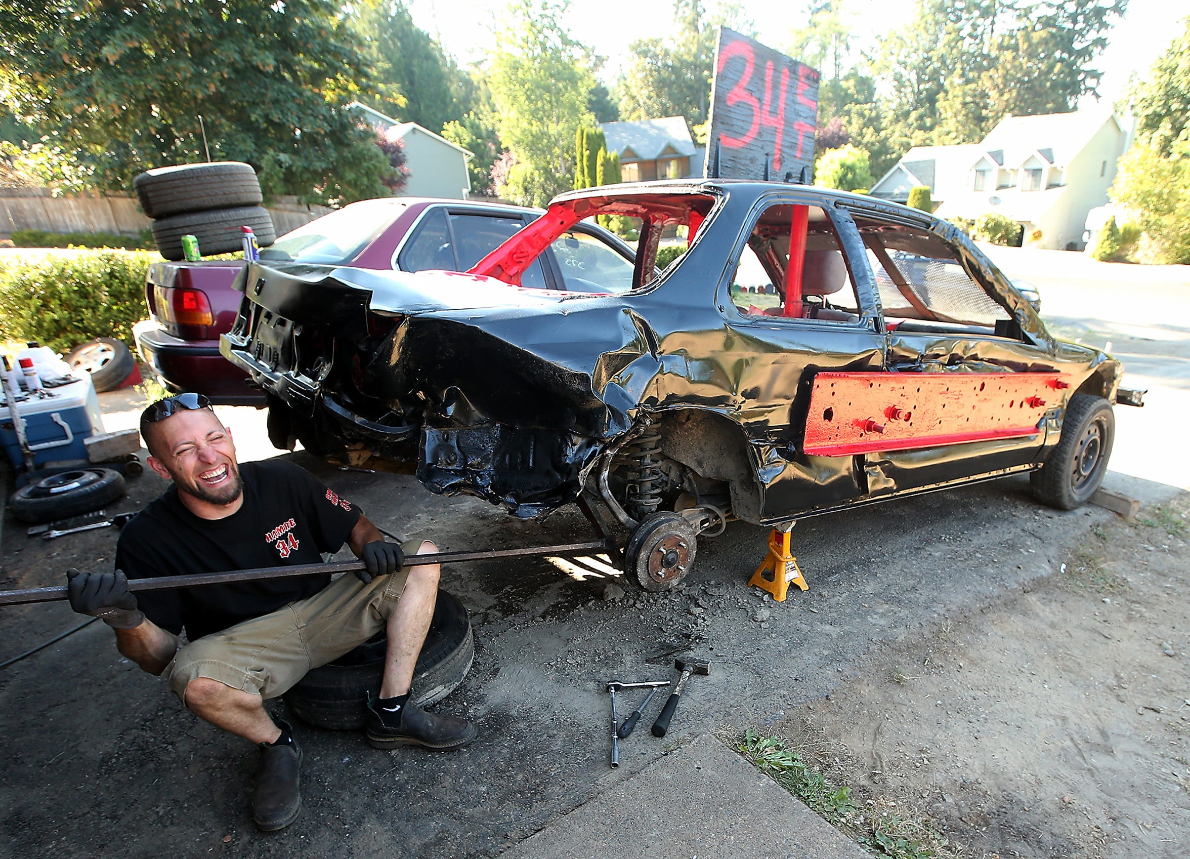Shane Hamre replaces the struts on his car at his home near Bremerton on July 26. Hamre, one of the more successful drivers in the Kitsap derby, makes a habit of handing out Matchbox cars to kids at the six events held each summer.