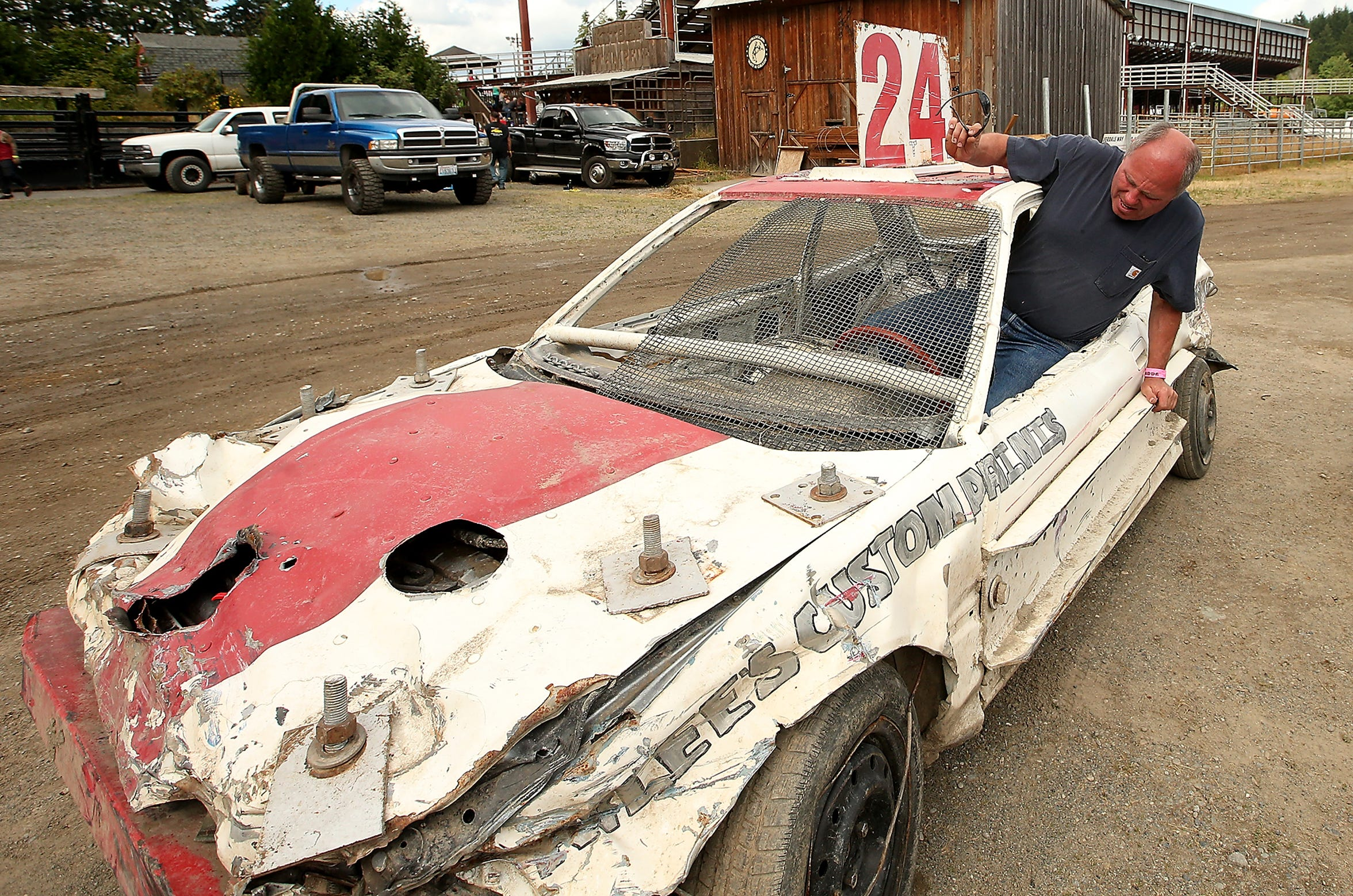 KC Straight slides into his mini car before time trials at the June 23 Kitsap Destruction Derby on Saturday. Straight, 57, has been driving in KDDA events for nearly 40 years.