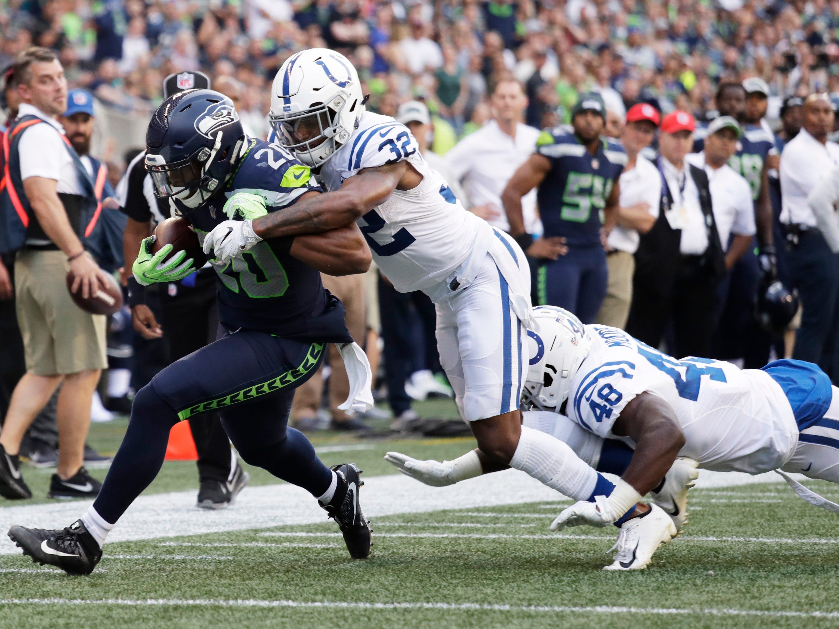 Seattle Seahawks running back Rashaad Penny (20) is tackled by Indianapolis Colts defensive back T.J. Green (32) during the first half of an NFL football preseason game, Thursday, Aug. 9, 2018, in Seattle. (AP Photo/Elaine Thompson)