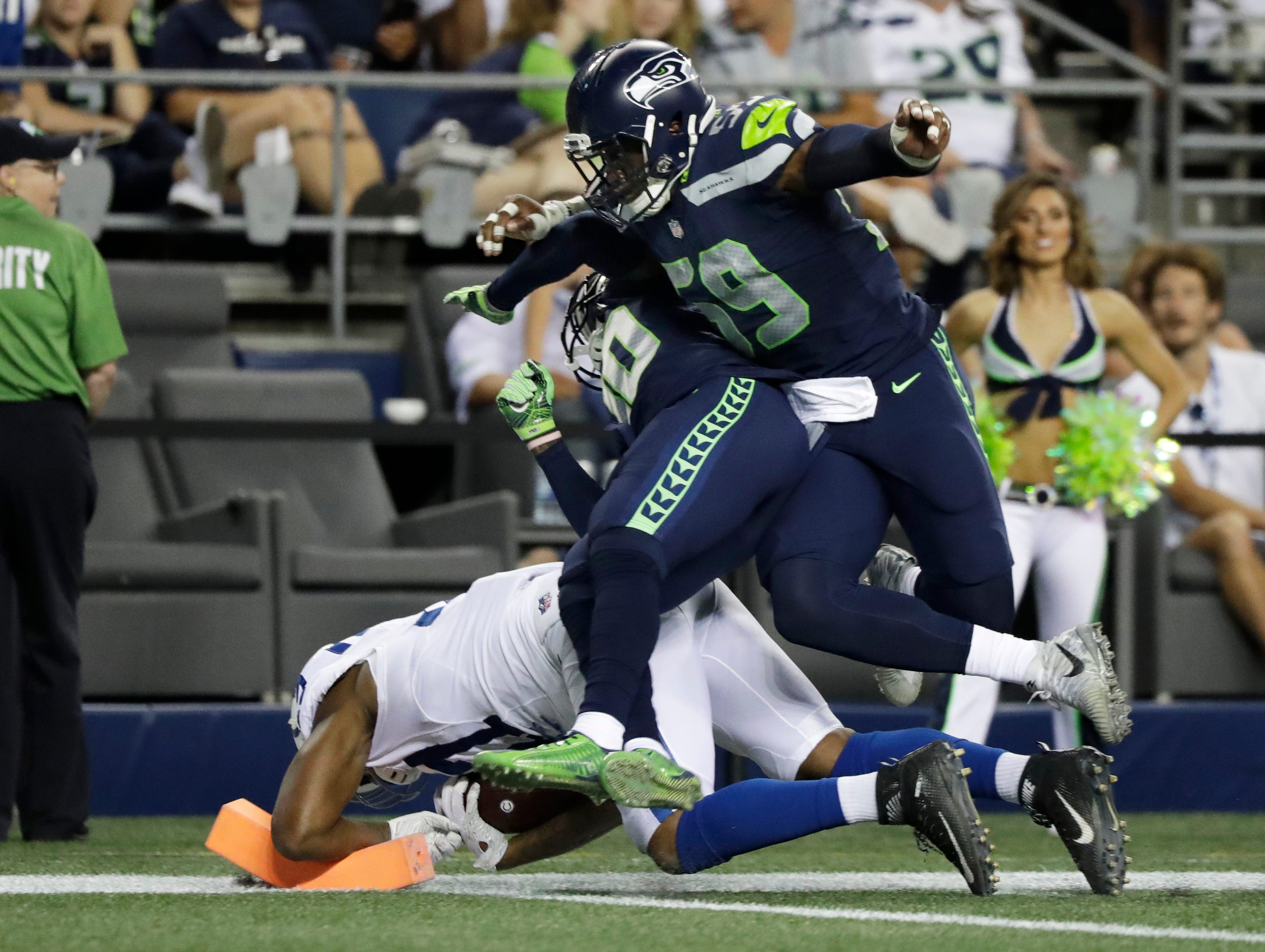Indianapolis Colts tight end Darrell Daniels, lower left, crashes into a pylon for a touchdown under the defense of Seattle Seahawks defensive end Jake Martin (59), and free safety Lorenzo Jerome, center, during the second half of an NFL football preseason game, Thursday, Aug. 9, 2018, in Seattle. (AP Photo/Elaine Thompson)