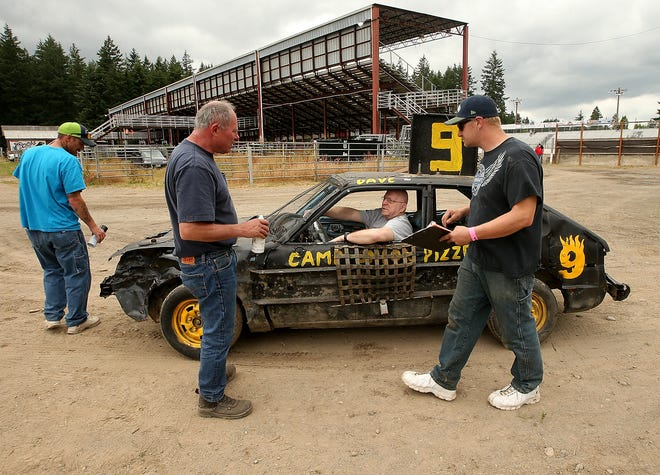 Kitsap Destruction Derby Association safety techs (left to right) Victor Trent, KC Straight and Dan Garrison walk around driver David Lake's (center) car as they perform a safety check prior to the start of the Kitsap Destruction Derby at Thunderbird Stadium on Saturday, June 23, 2018.