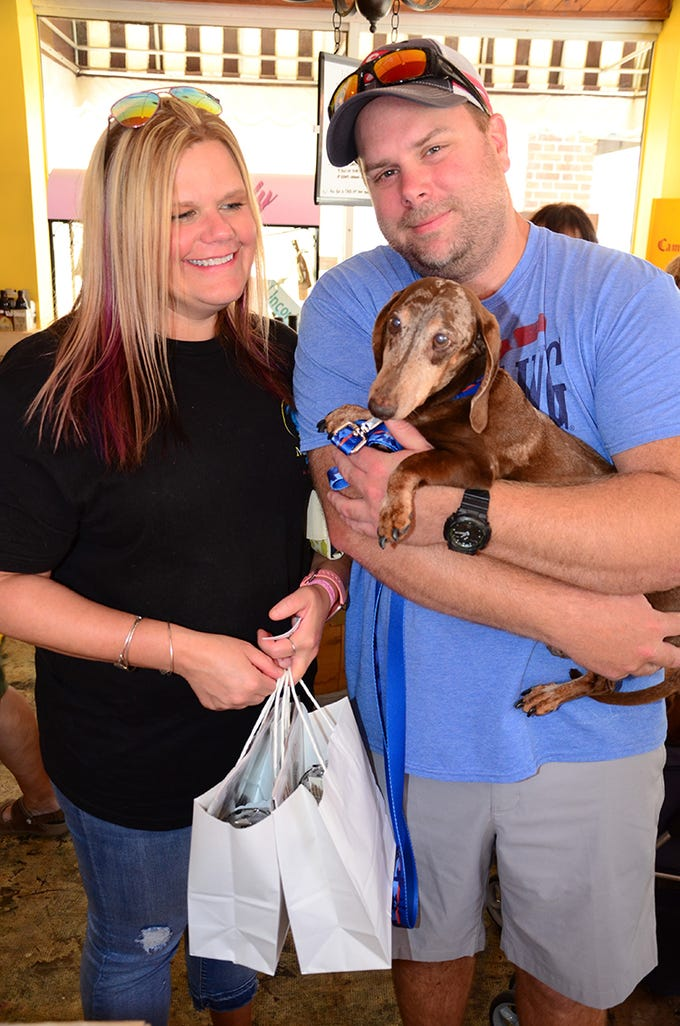 Michelle Dullard, Chipper, and Matt Callaghan pose Saturday during the Florida Dachshund Rescue benefit hosted by Tails at the Barkery, with the venue being The Wine Lady in Cocoa Village.