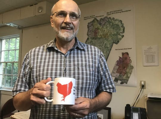 "Ken Belliveau, Williston's director of planning and zoning, displays his office ""chicken-zoning"" mug on Thursday, Aug. 9, 2018."