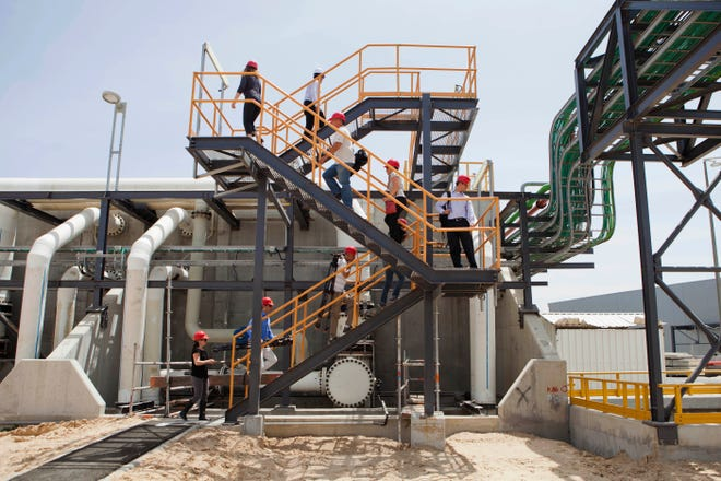 In this Sunday, May 4, 2014 photo, workers climb stairs at the Sorek desalination plant in Rishon Letzion, Israel. Israel's aggressive desalination program that has transformed this perennially parched country into perhaps the most well-hydrated country in the region. (AP Photo/Dan Balilty)