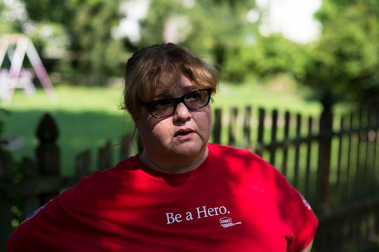 Anna Simpkins, a nine-year Lowe's employee whose own family has been affected by Burlington County's opioid epidemic, stands in the yard as she and her team work to rehab the yard of the Kenny Smith Freedom House, a sober living home Friday, Aug. 10, 2018 in Marlton, N.J.
