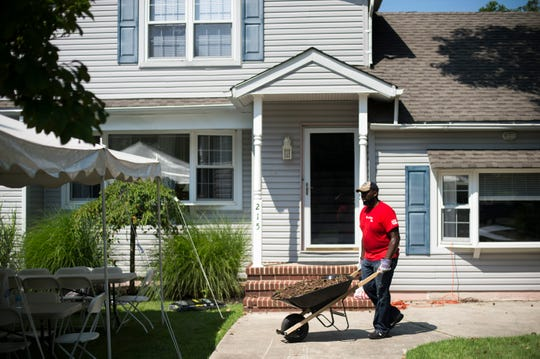 Shaheed Sellers, a volunteer with Lowe's, works to rehab the yard of the Kenny Smith Freedom House, a sober living home Friday, Aug. 10, 2018 in Marlton, N.J.