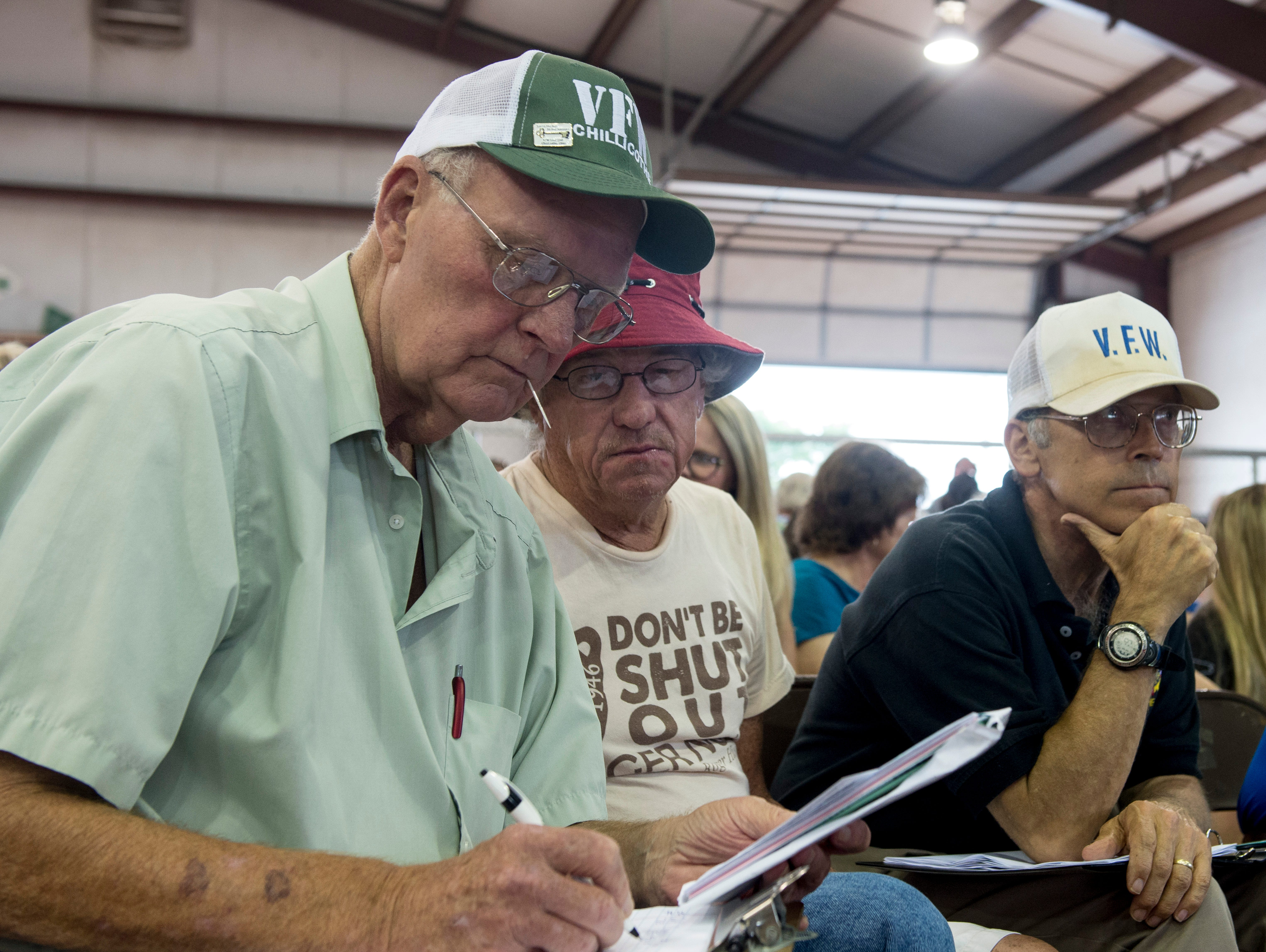 Members of the crowd  lookover the list of hogs available for auction during the Junior Fair Swine Sale at the Ross County Fair on August 9, 2018 in Chillicothe, Ohio.
