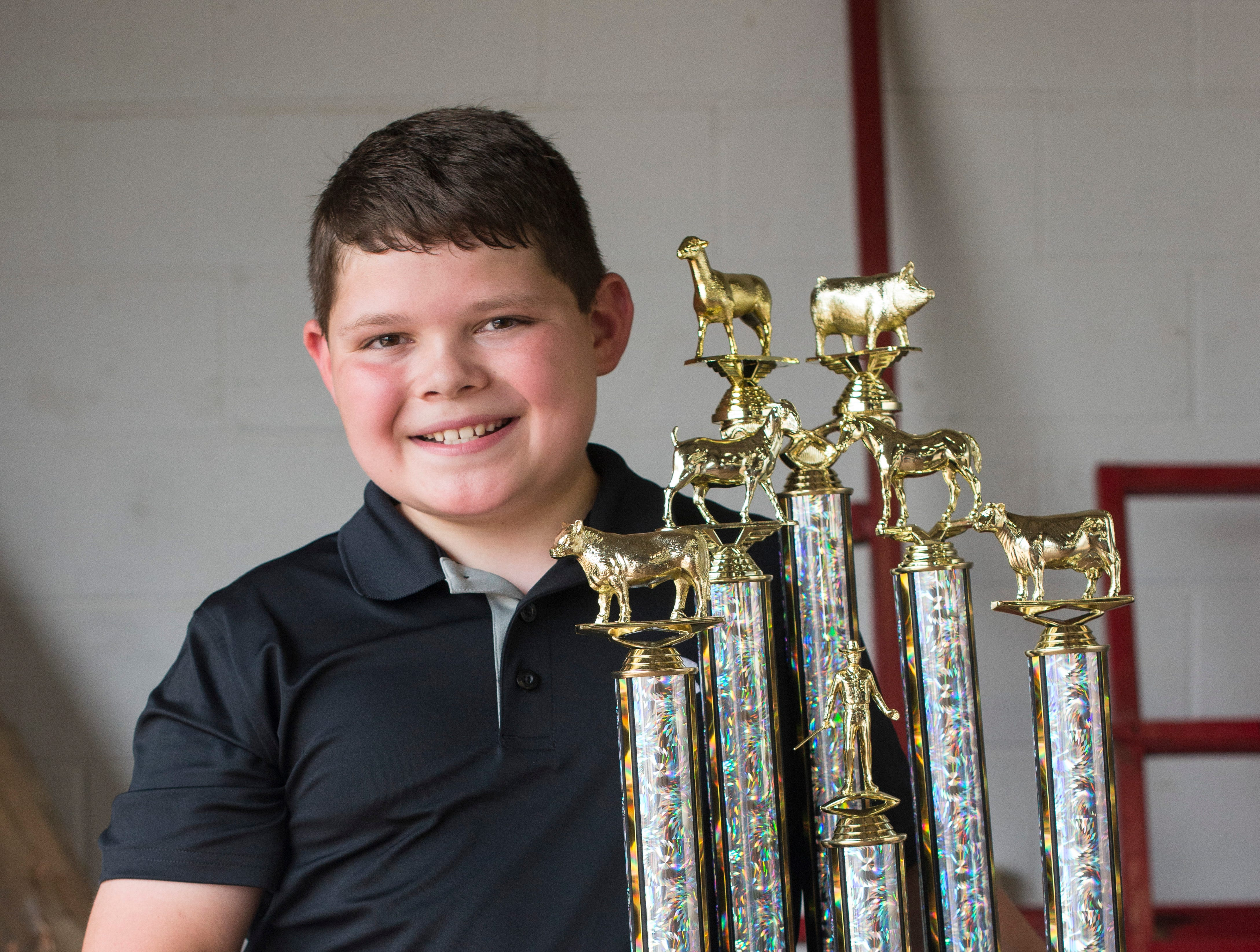 Hayden Good, winner of the junior class, poses with his trophy following the conclusion of the Showman of Showmen Contest in Large Animals at the Ross County Fair on August 10, 2018, in Chillicothe, Ohio.