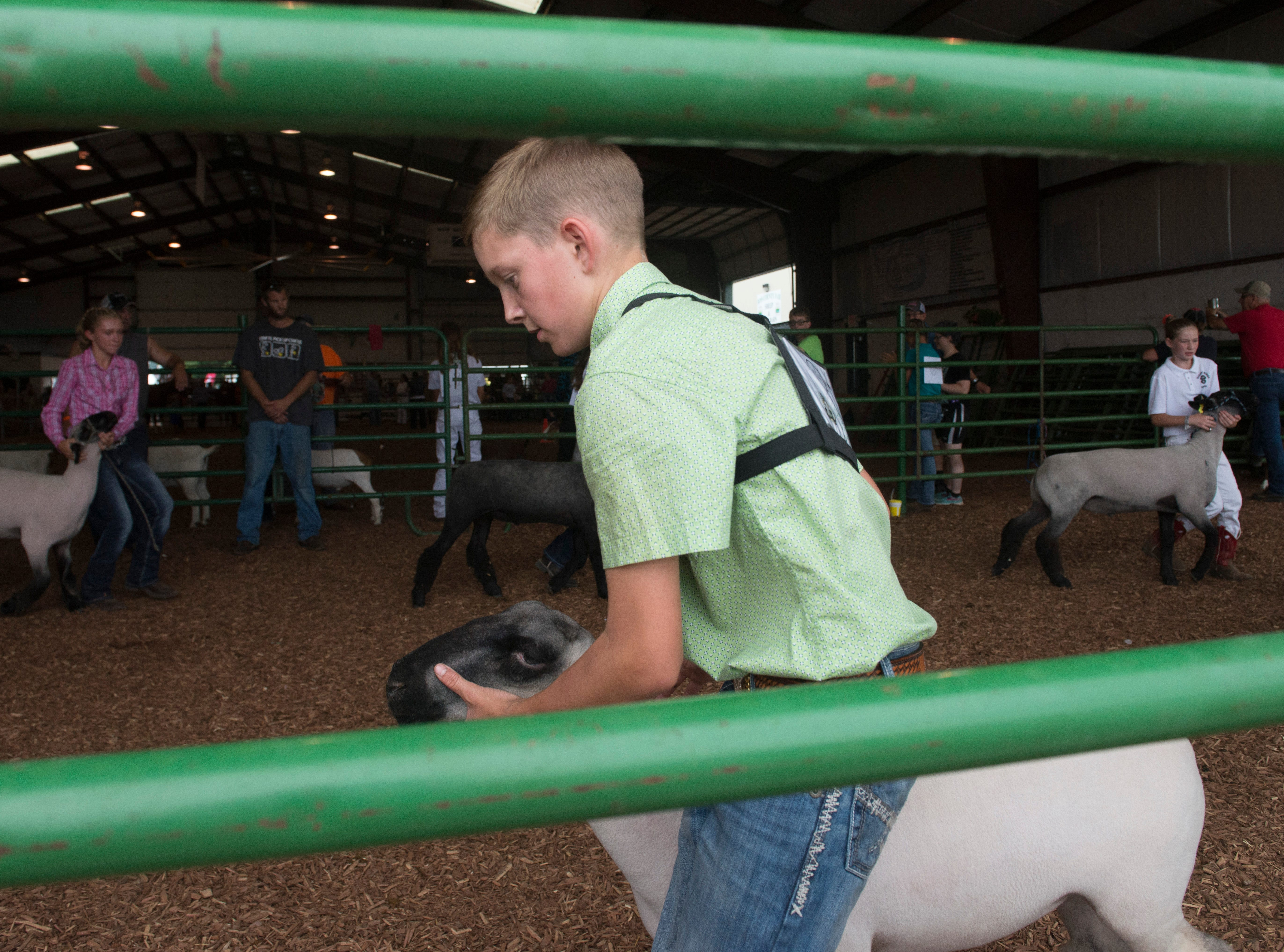 Judson Drake, intermediate contestant, works with a sheep during the Showman of Showmen Contest in Large Animals at the Ross County Fair on August 10, 2018, in Chillicothe, Ohio.