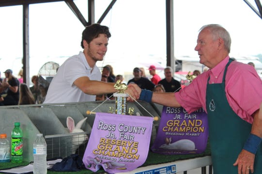 Josh Morgan, 19, from the Clarksburg Jolly Beef Feeders shakes the hand of a judge after receiving Grand and Reserve Champion honors in the breeding rabbits category at the Ross County Fair on Wednesday.