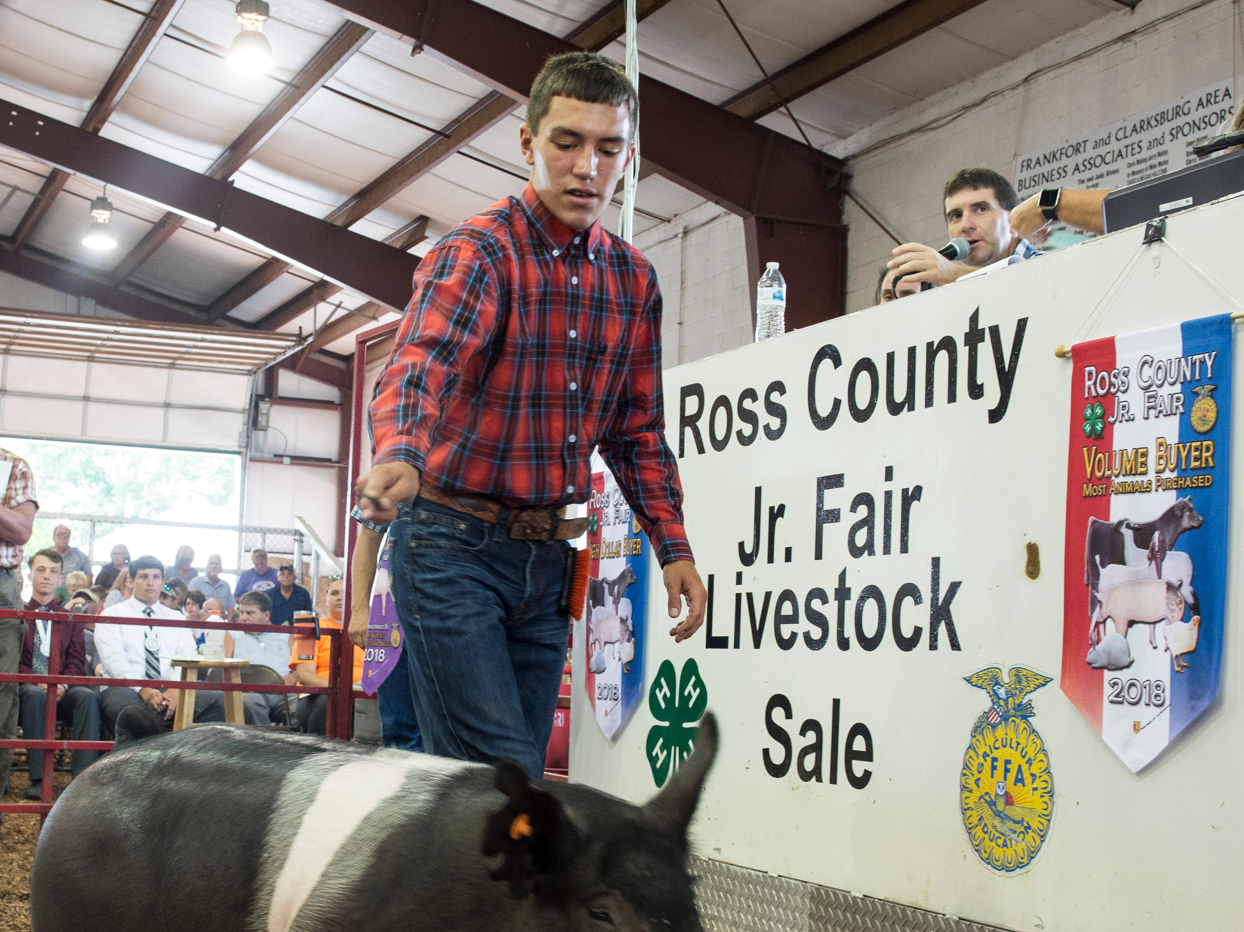 Garrett Simmons displays his 261-pound hog during the Junior Fair Swine Sale at the Ross County Fair on August 9, 2018 in Chillicothe, Ohio. The hog was selected as the 2018 Grand Champion Market Hog.