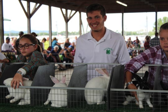 Kenton Richter shows off his rabbits Wednesday morning for the Jr. Fair Cavy and Rabbit judging at the Ross County Fair.