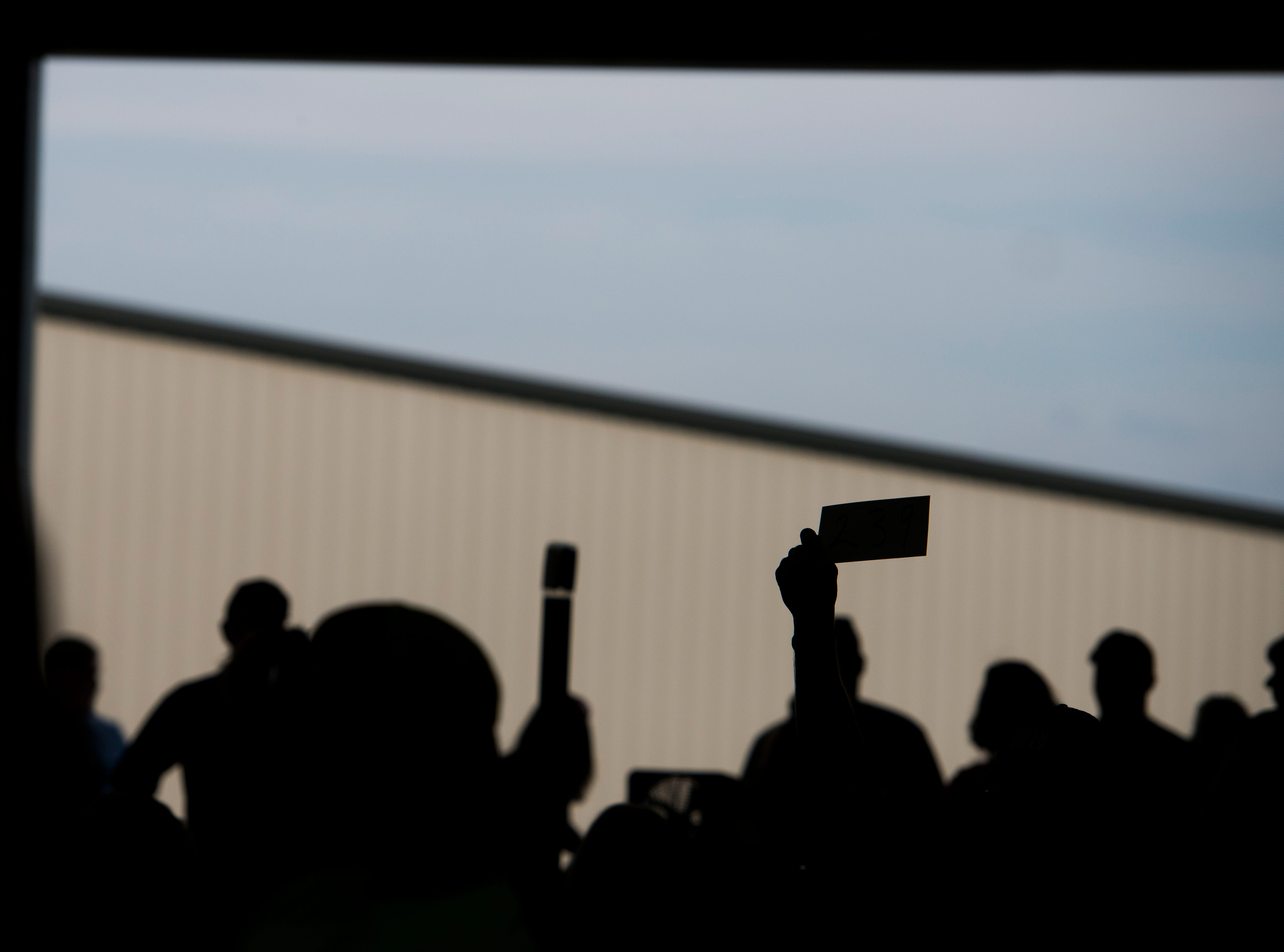 A member of the crowd lifts their ticket to bid during the Junior Fair Swine Sale at the Ross County Fair on August 9, 2018 in Chillicothe, Ohio.