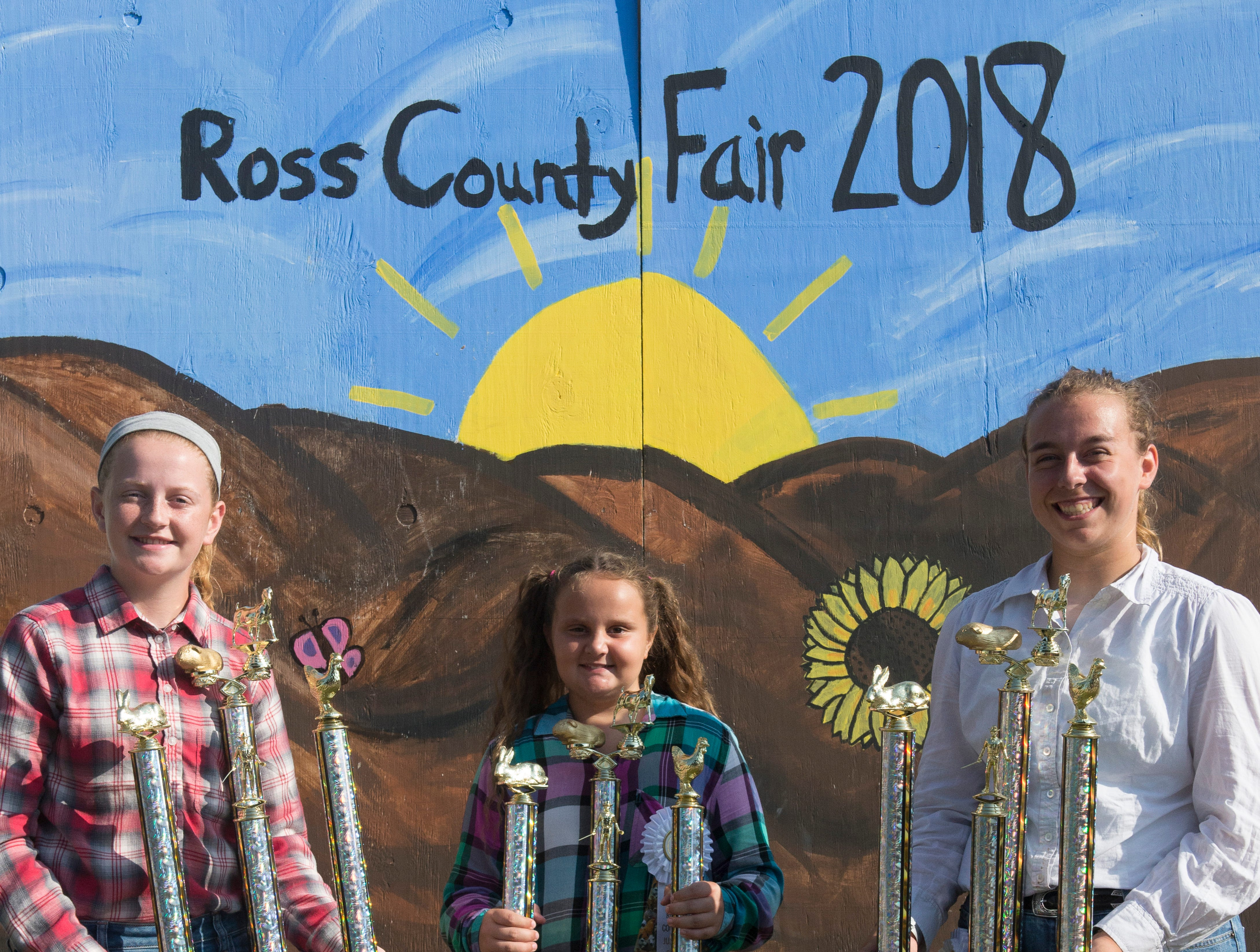From left: first place winner of the intermediate class; Cambriana Rittinger, 9, first place winner of the junior class; and Ruth Beery, first place winner of the senior class, pose after the conclusion of the Small Animal Showman of Showmen Contestat the Ross County Fair on August 9, 2018 in Chillicothe, Ohio.