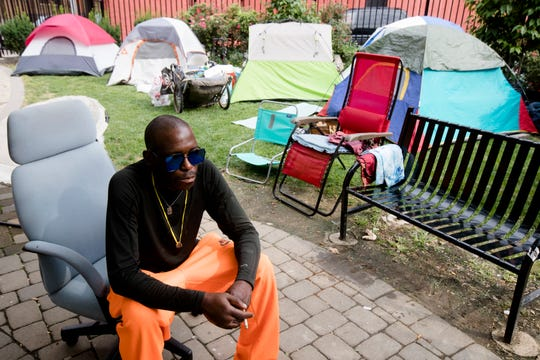 Desmond Brown sits at a homeless encampment he is staying in at a private park off of 13th street in Over The Rhine on Friday, Aug. 10, 2018.