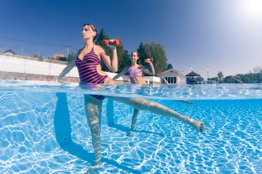 Women Exercising With Dumbbells In Swimming Pool