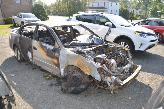 The Nissan Altima car destroyed by fire after striking a fire hydrant, street sign and tree along Route 22 in Mountainside.