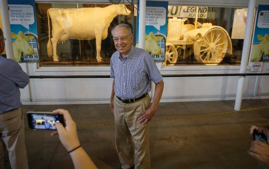 U.S. Sen. Charles Grassley (R-Iowa) poses for a photo near the butter cow on Friday, Aug. 10, 2018, during the Iowa State Fair in Des Moines.