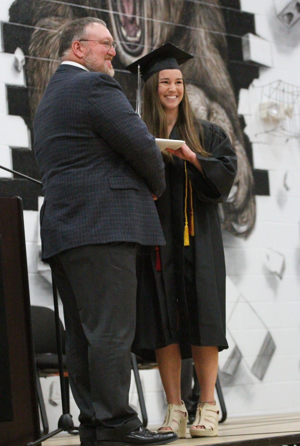 Mollie Tibbetts receives her diploma from Ed Kline, BGM school board president, during the 2017 commencement ceremonies.