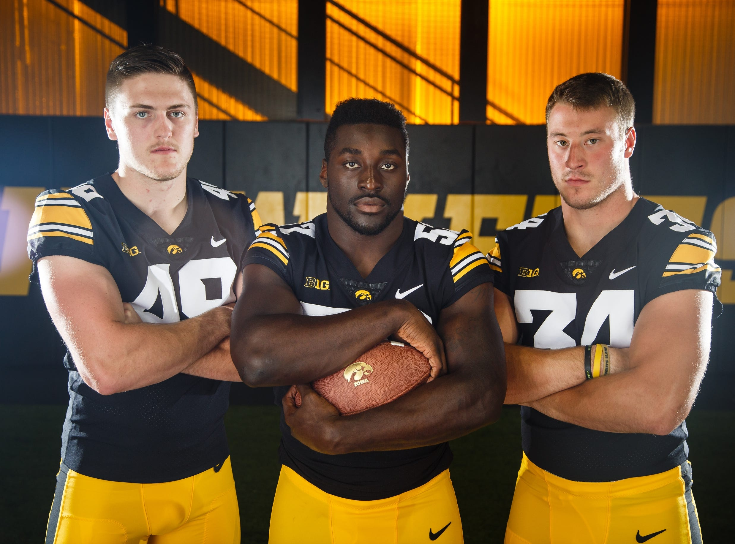 Iowa's Nick Niemann, left, Amani Jones, center, and Kristian Welch, right, pose for a photo during the Iowa Football media day on Friday, Aug. 10, 2018 in Iowa City.