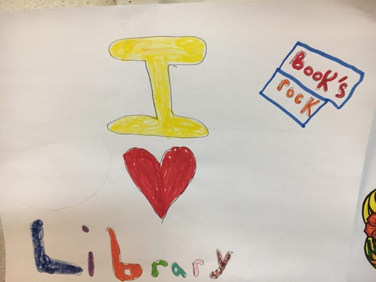 A child draws how he feels about the Linden Public Library.
