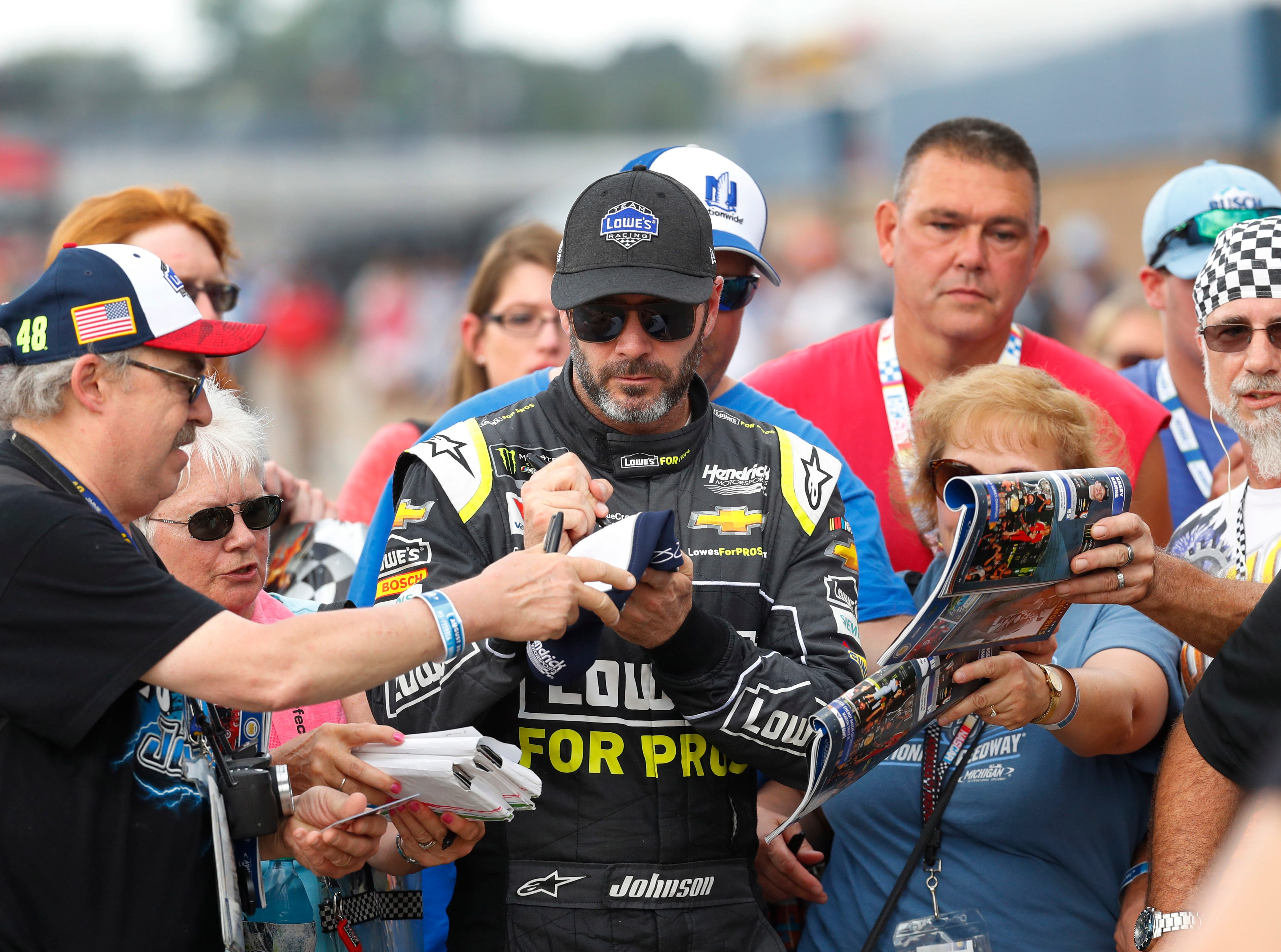 Jimmie Johnson signs autographs during qualifications for a NASCAR Cup Series auto race at Michigan International Speedway in Brooklyn, Mich., Friday, Aug. 10, 2018. (AP Photo/Paul Sancya)