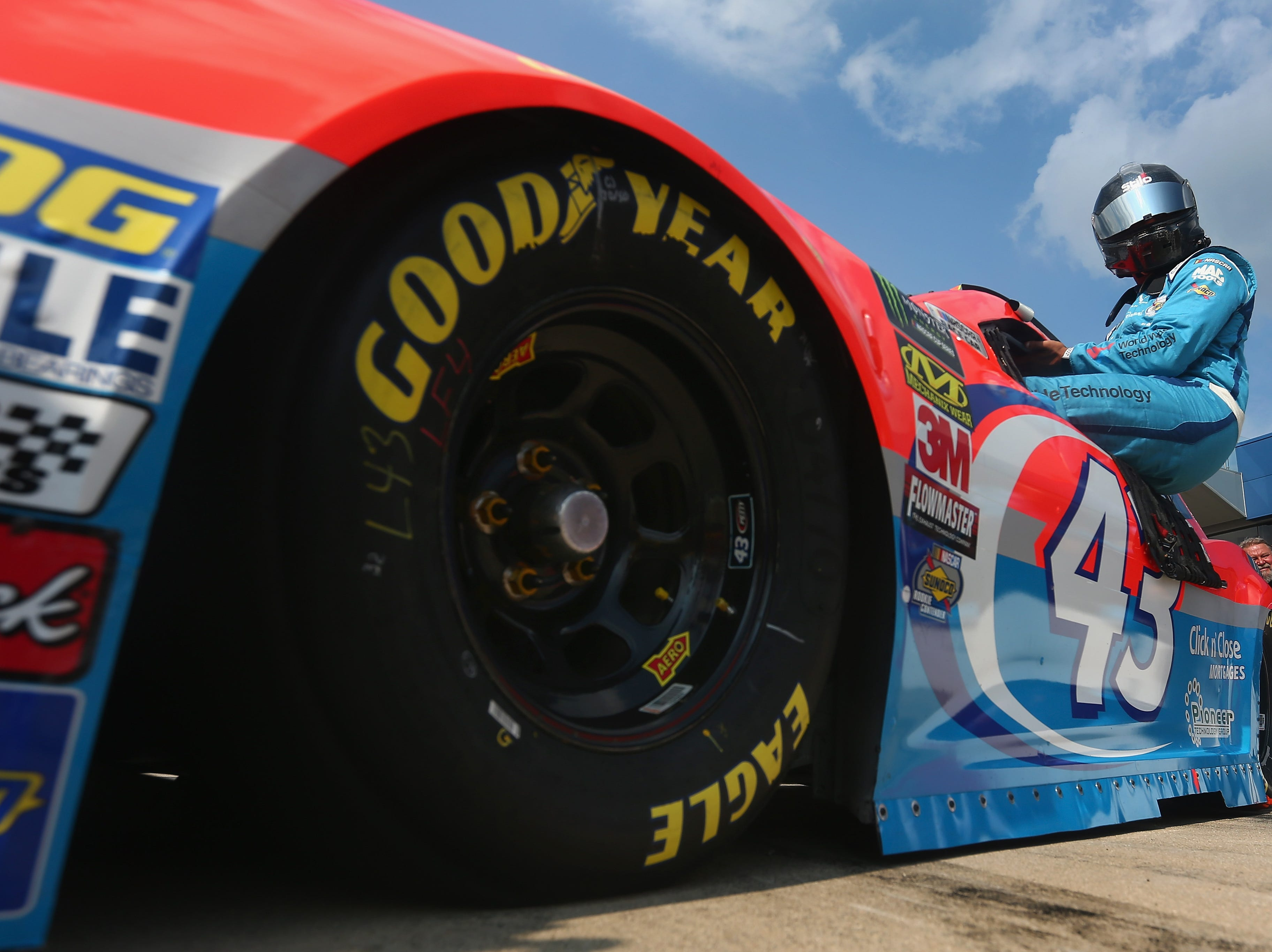 Bubba Wallace, driver of the #43 Medallion Bank/Petty's Garage Chevrolet, climbs into his car during qualifying for the Monster Energy NASCAR Cup Series Consmers Energy 400 at Michigan International Speedway on August 10, 2018 in Brooklyn, Michigan.