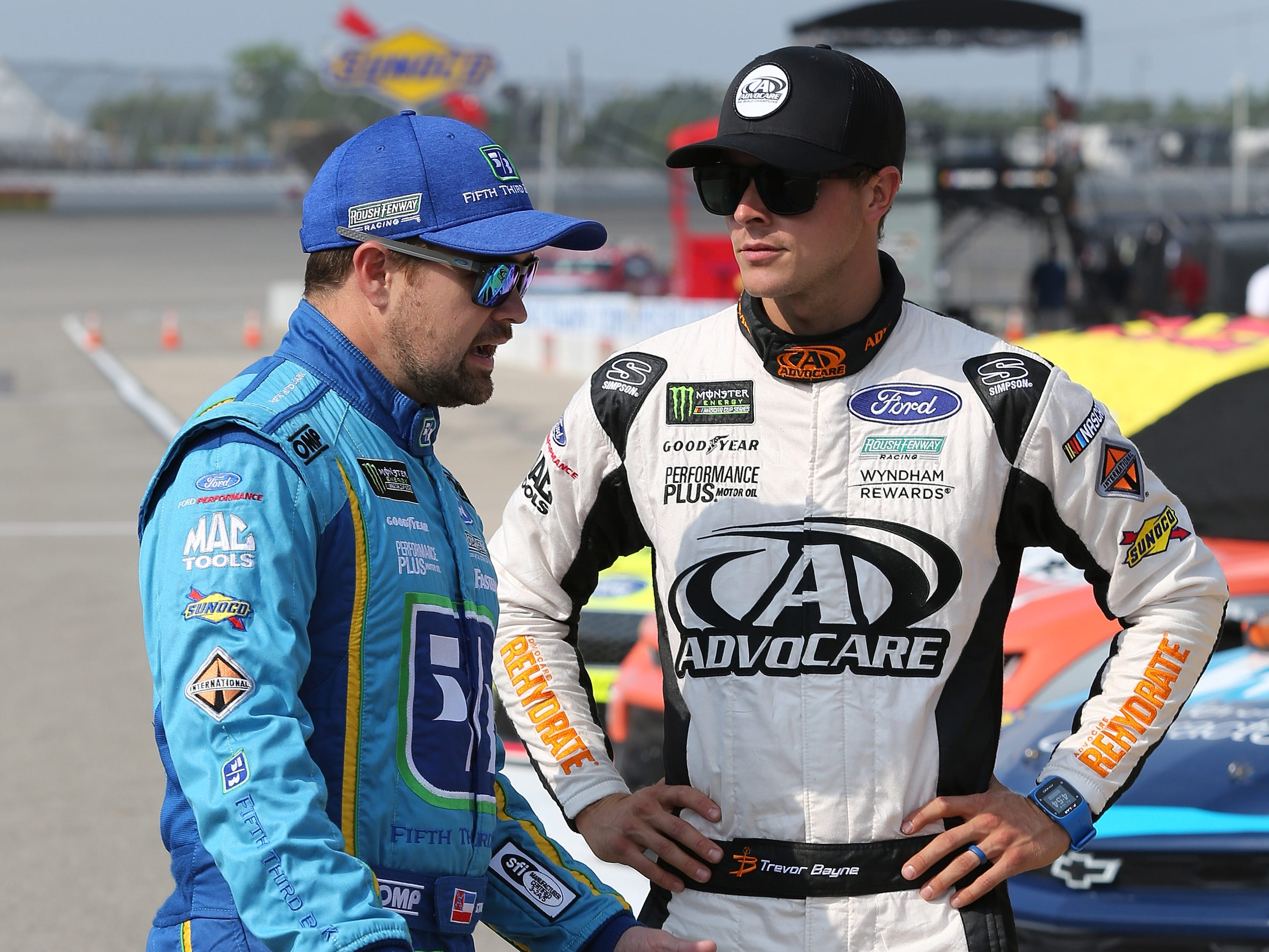 Ricky Stenhouse Jr., driver of the #17 Fifth Third Bank Ford, and Trevor Bayne, driver of the #6 AdvoCare Rehydrate Ford, talk during qualifying for the Monster Energy NASCAR Cup Series Consmers Energy 400 at Michigan International Speedway on August 10, 2018 in Brooklyn, Michigan.