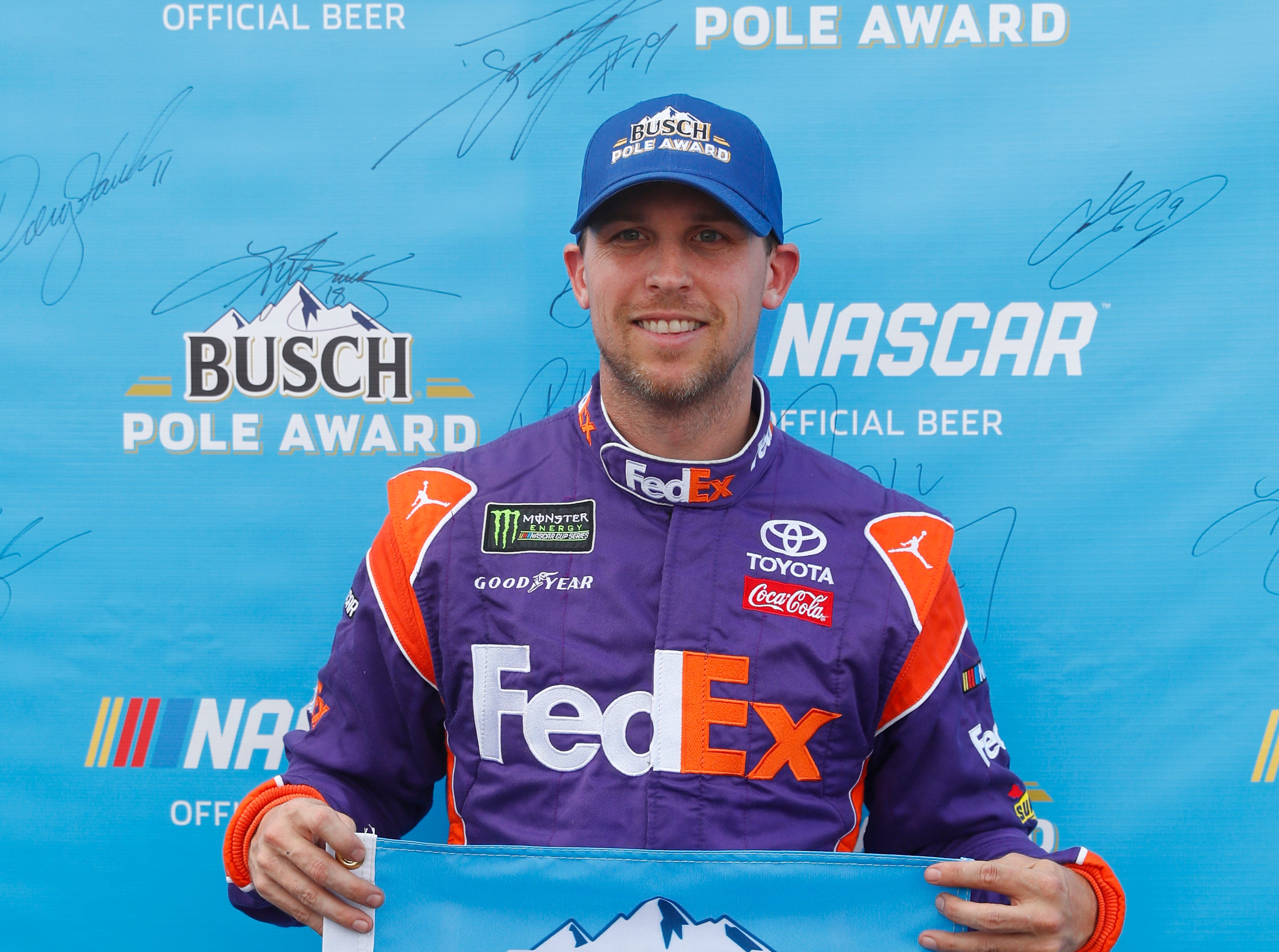 Denny Hamlin holds the pole award after qualifications for a NASCAR Cup Series auto race at Michigan International Speedway in Brooklyn, Mich., Friday, Aug. 10, 2018.