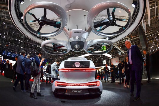 "The ""Pop.Up Next"" concept flying car,  by Audi, italdesign and Airbus, was displayed at  the 2018 Geneva Motor Show in March.  Its passenger cabin can fit onto either an autonomous driving electric car, or a flight module with vertical takeoff and landing."